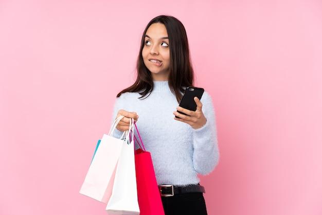 Jonge vrouw met boodschappentas over geïsoleerde roze achtergrond met koffie om mee te nemen en een mobiel terwijl ze iets denkt