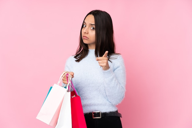 Jonge vrouw met boodschappentas over geïsoleerde roze gefrustreerde achtergrond en naar voren wijzend