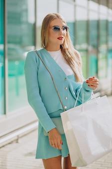 Jonge vrouw met boodschappentassen bij het winkelcentrum