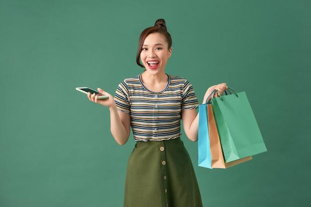 Jonge vrouw met boodschappentassen en een mobiele telefoon
