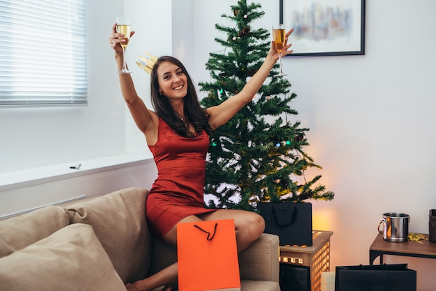 Jonge vrouw met boodschappentassen in de buurt van de kerstboom.