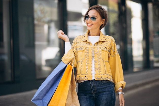 Jonge vrouw met boodschappentassen in de stad