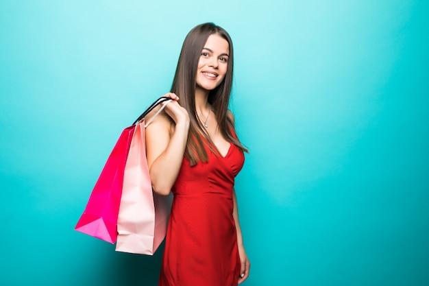 Jonge vrouw met boodschappentassen in rode jurk op blauwe muur