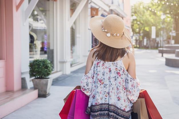 Jonge vrouw met boodschappentassen in winkelcentrum op zwarte vrijdag