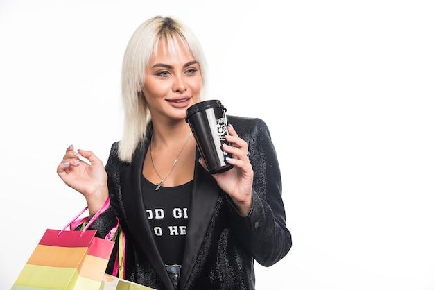 Jonge vrouw met boodschappentassen kopje koffie drinken op witte achtergrond. hoge kwaliteit foto