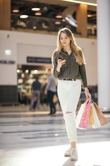 Jonge vrouw met boodschappentassen met behulp van haar slimme telefoon om te kopen