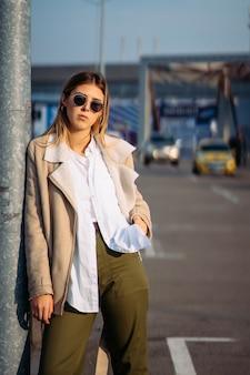 Jonge vrouw met boodschappentassen op een bushalte