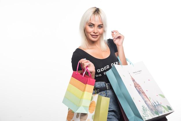 Jonge vrouw met boodschappentassen op witte muur.