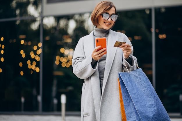 Jonge vrouw met boodschappentassen praten aan de telefoon