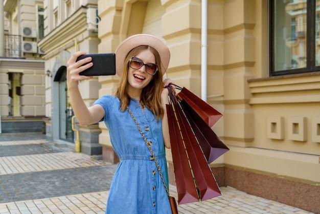 Jonge vrouw met boodschappentassen selfie wandelen in een stad op zomerdag maken