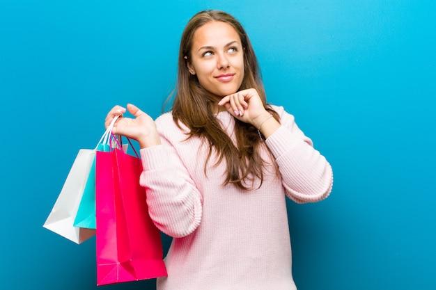 Jonge vrouw met boodschappentassen tegen blauwe achtergrond