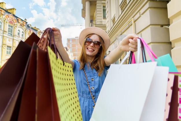 Jonge vrouw met boodschappentassen wandelen in een stad op zomerdag