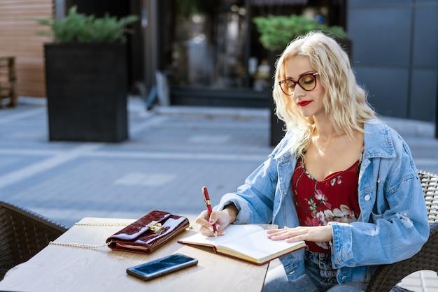 Jonge vrouw met bril, een freelancer zit aan een tafel in een café op straat en schrijft in een notitieblok
