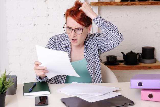 Jonge vrouw met bril met rood kort haar is geschokt door wat ze ziet in de officiële documenten