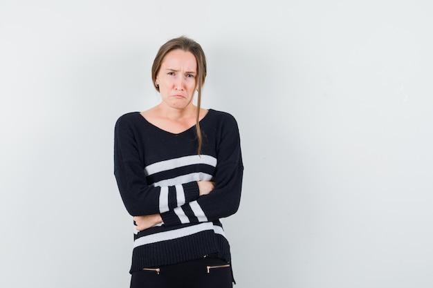 Jonge vrouw met buikpijn in gestreepte breigoed en zwarte broek en uitgeput op zoek