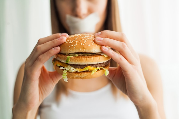 Jonge vrouw met buisband over haar mond, die haar verhinderen om ongezonde kost, gezond het eten concept te eten