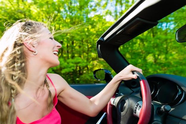 Jonge vrouw met cabriolet in de zomer op dagtocht