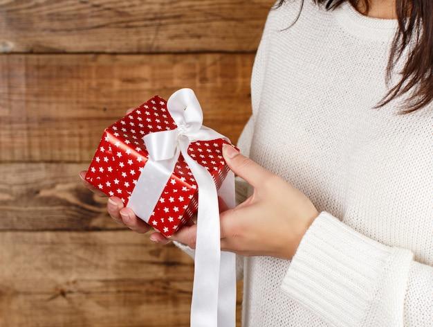 Jonge vrouw met cadeau-pakket in handen close-up