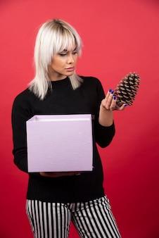 Jonge vrouw met cadeautjes met een grote dennenappel op een rode achtergrond. hoge kwaliteit foto