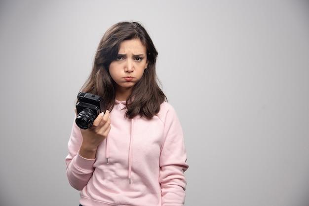Jonge vrouw met camera die verdrietig is.