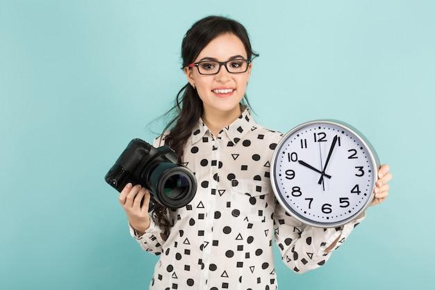 Jonge vrouw met camera en klokken