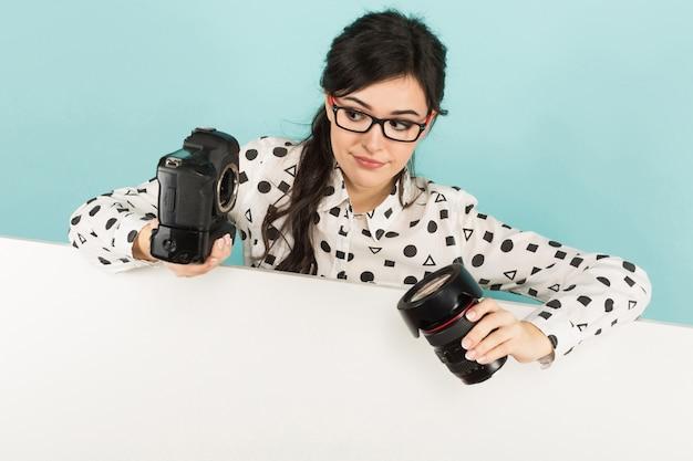 Jonge vrouw met camera en lens