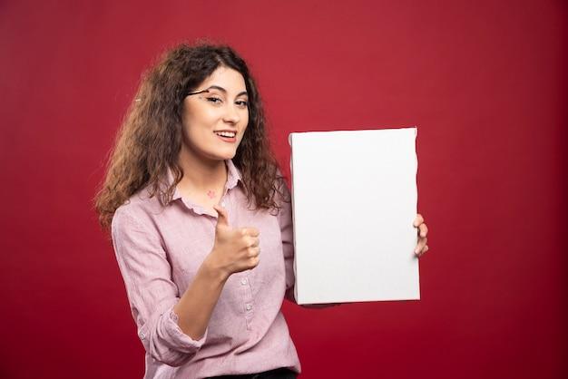 Jonge vrouw met canvas duimen opgevend
