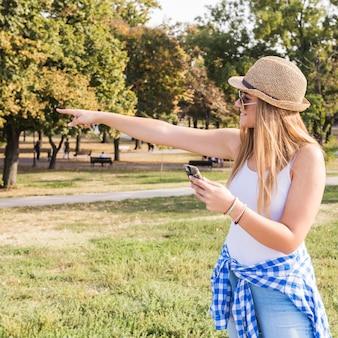 Jonge vrouw met cellphone die op iets richt