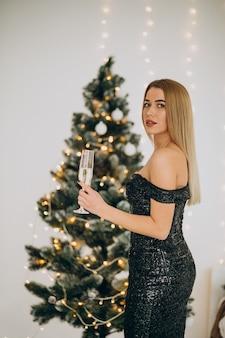 Jonge vrouw met champagne bij de kerstboom