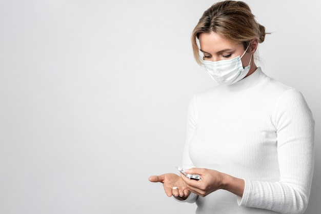 Jonge vrouw met chirurgisch masker dat tabletten neemt