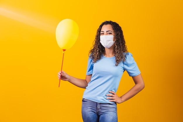 Jonge vrouw met chirurgisch masker die een gele ballon houdt.