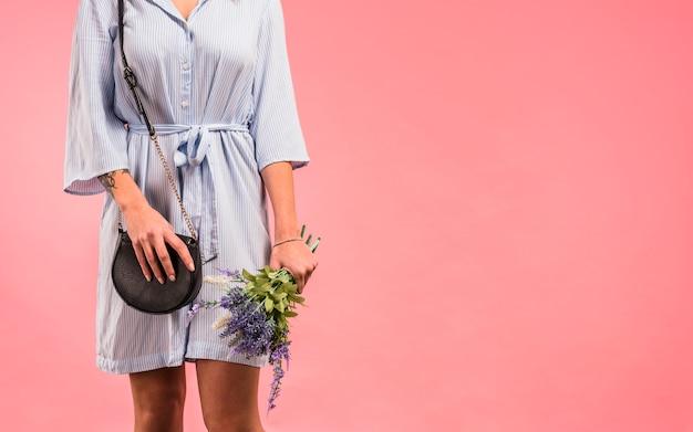 Jonge vrouw met clutch bag en bloemen