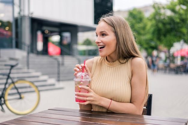 Jonge vrouw met cocktail in straatcafé