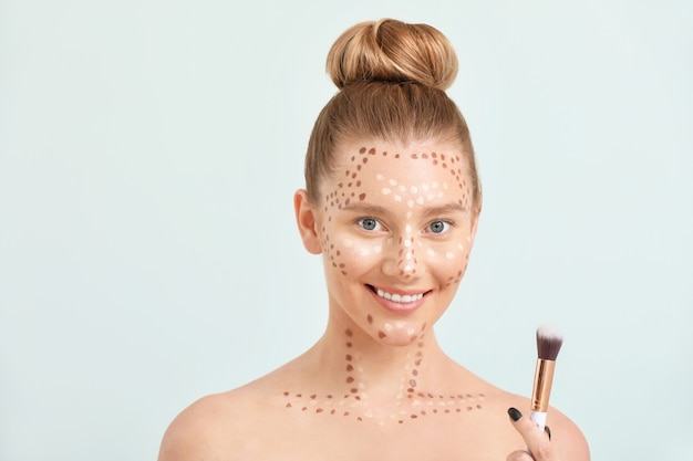Jonge vrouw met contouring make-up en penseel op licht