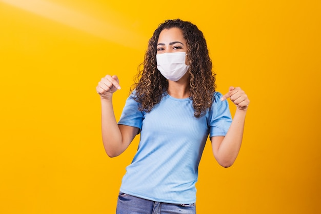 Jonge vrouw met coronavirus beschermend masker wijzend op haar t-shirt
