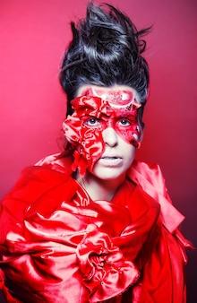Jonge vrouw met creatief rood gezichtsart