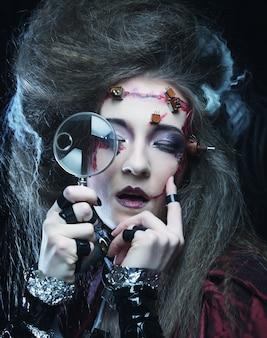 Jonge vrouw met creatieve make-up die een vergrootglas vasthoudt