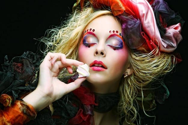 Jonge vrouw met creatieve make-up in poppenstijl met cake.