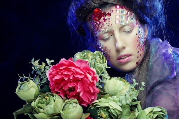 Jonge vrouw met creatieve make-up met bloemen