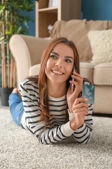 Jonge vrouw met creditcard die op mobiele telefoon thuis spreekt. online winkelen