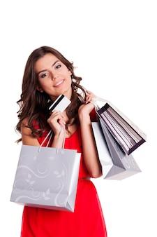 Jonge vrouw met creditcard en boodschappentassen