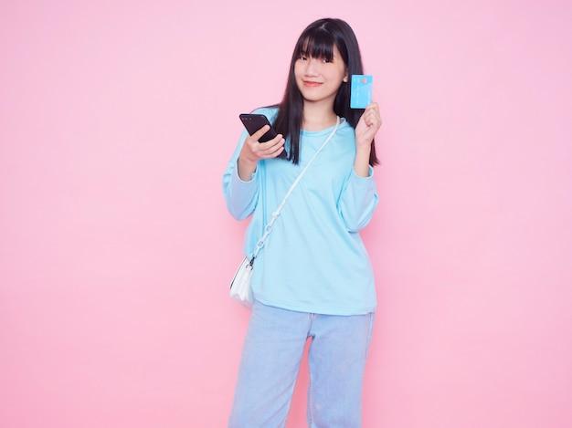 Jonge vrouw met creditcard en smartphone op roze muur. online winkelen
