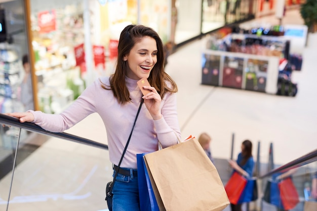 Jonge vrouw met creditcard en volle boodschappentassen