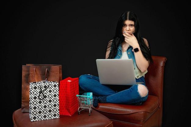 Jonge vrouw met creditcard met behulp van laptop voor online winkelen, geïsoleerd op zwart