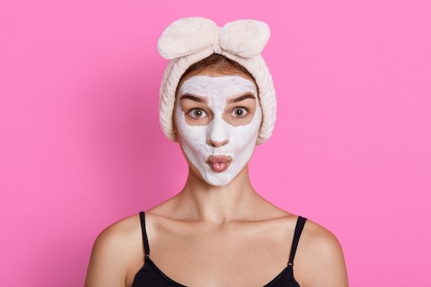 Jonge vrouw met crème masker op haar gezicht en haarband op hoofd, meisje met afgeronde lippen terwijl poseren tegen roze muur.