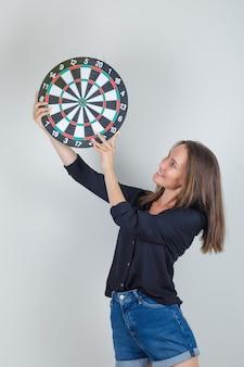 Jonge vrouw met dartbord in zwart shirt, jeans broek en op zoek vrolijk