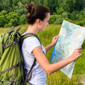 Jonge vrouw met de groene kaart van de rugzaklezing op wandeltocht in openlucht