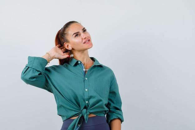 Jonge vrouw met de hand achter het hoofd, opzoeken in groen shirt en dromerig kijken, vooraanzicht.