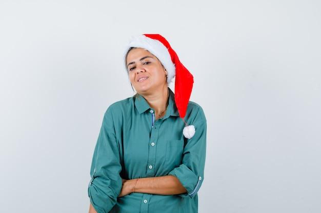 Jonge vrouw met de hand op de buik in shirt, kerstmuts en zelfverzekerd kijken. vooraanzicht.