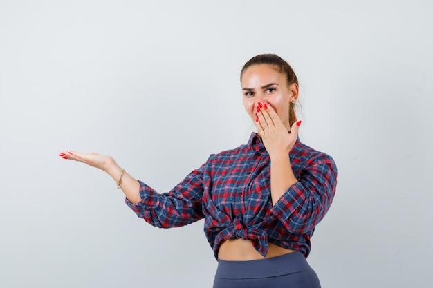Jonge vrouw met de hand op de mond terwijl ze iets in een geruit hemd, een broek laat zien en er verbaasd uitziet. vooraanzicht.